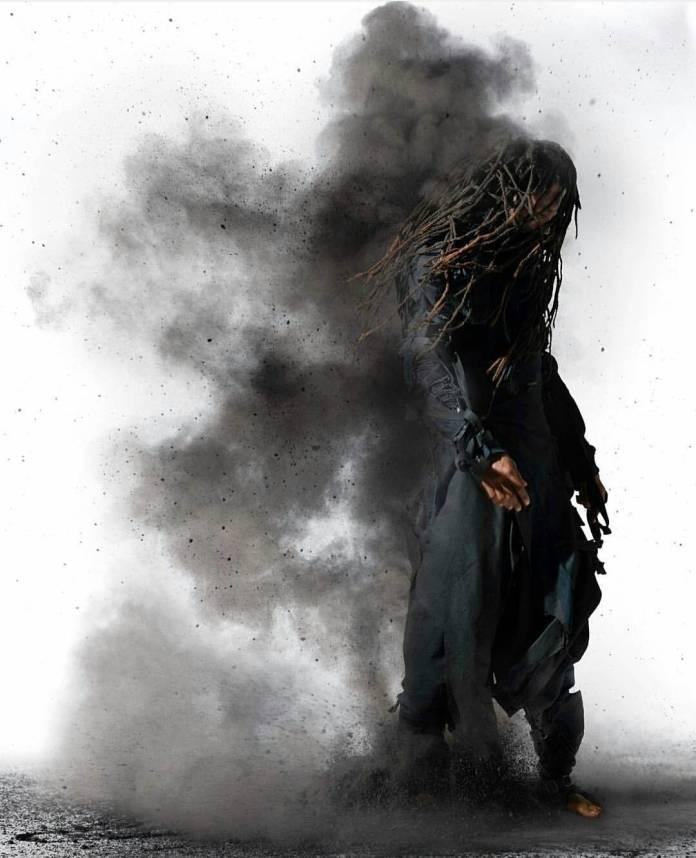 Black man standing, a cloud of black dust behind him described as Pan and seen on Nubiamancy